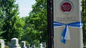 Blue and white ribbons flutter on a gate column at Oak Hill Cemetery in preparation for Otto Warmbier's funeral in Cincinnati on Wednesday, June 21, 2017. (AP Photo/Dake Kang)