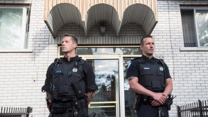 Police stand guard in front of an apartment building in Montreal, Wednesday, June 21, 2017. (Paul Chiasson / THE CANADIAN PRESS)