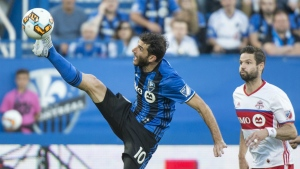 Montreal Impact midfielder Ignacio Piatti kicks the ball in front of Toronto FC defender Drew Moor during first half of the first leg of the Canadian Championship soccer final action, in Montreal on Wednesday, June 21, 2017. (Paul Chiasson / THE CANADIAN PRESS)a