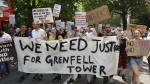 Demonstrators hold a banner demanding justice for the victims of the recent deadly fire at Grenfell Tower apartment block as they march towards parliament in central London on Wednesday, June 21, 2017. (AP / Matt Dunham)