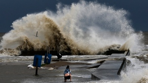 Sydney Schultz takes photos of waves crashing next to Rollover Pass as Tropical Storm Cindy approaches the Bolivar Peninsula, on June 21, 2017. (Michael Ciaglo / Houston Chronicle via AP)