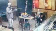 A suspect in a rash of armed robberies points a rifle at a woman and young child inside a Subway restaurant in this surveillance camera image. (Toronto Police Service)