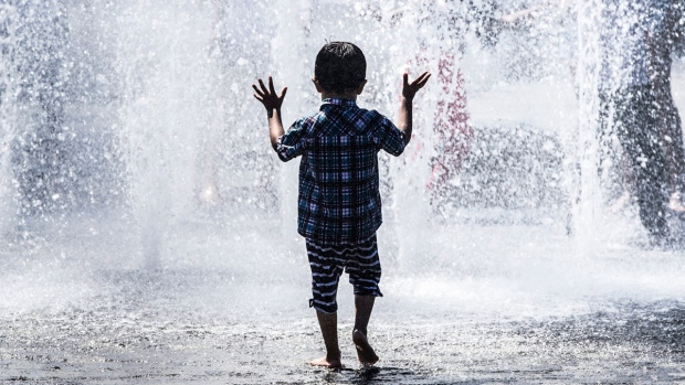 Playing in a water fountain on the hottest day of the year to date, in Bradford, England, on June 17, 2017. (Danny Lawson/PA via AP)