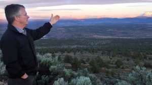 Joe Krenowicz, executive director of the Madras-Jefferson County Chamber of Commerce, gestures toward Mt. Jefferson as the sun rises over Madras, Oregon on June 13, 2017.  (AP Photo/Gillian Flaccus)