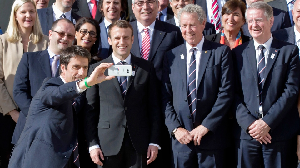 Paris Mayor Anne Hidalgo,center, and the co-president of the Paris bid for the 2024 Olympics Tony Estanguet take a selfie as they paddle on the Seine river in Paris Friday, June 23, 2017. (Martin Bureau, Pool via AP)