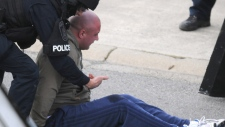 Jamie Bacon, who police say is a notorious gang member, is handcuffed outside his home in Abbotsford, B.C., Friday, April 3, 2009(John Van Putten/The Abbotsford News).
