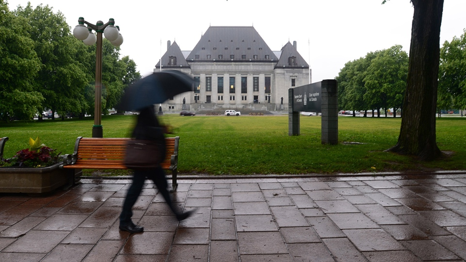 A pedestrian walks in the rain past the Supreme Court of Canada in Ottawa on Friday, June 23, 2017. (Sean Kilpatrick / THE CANADIAN PRESS)