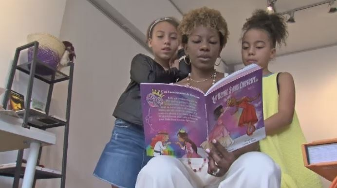 Tamara Beliard-Rodriguez reads her book 'Hair to the Queen' to her daughters.