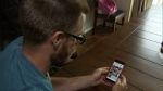 Devin Perfect scrolls through gif images on his smartphone. (CTV)