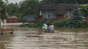With their road flooded out in Drayton, these two people took to a canoe. (Rosie Joostema, Drayton)