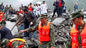Emergency personnel and local people work at the site of a landslide in Xinmo village in Maoxian County in southwestern China's Sichuan Province, Saturday, June 24, 2017.(Chinatopix via AP)