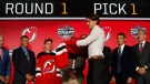 Center Nico Hischier, chosen by the New Jersey Devils in the first round of the NHL hockey draft, puts on a jersey Friday, June 23, 2017, in Chicago. (THE CANADIAN PRESS/AP-Nam Y. Huh)