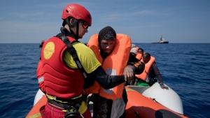 FILE -- In this April 6, 2017, Proactiva Open Arms lifeguard Ivan Martinez, from Spain, rescues migrants from a rubber boat sailing out of control, in the Mediterranean sea, about 56 miles north of Sabratha, Libya. (AP Photo/Bernat Armangue)