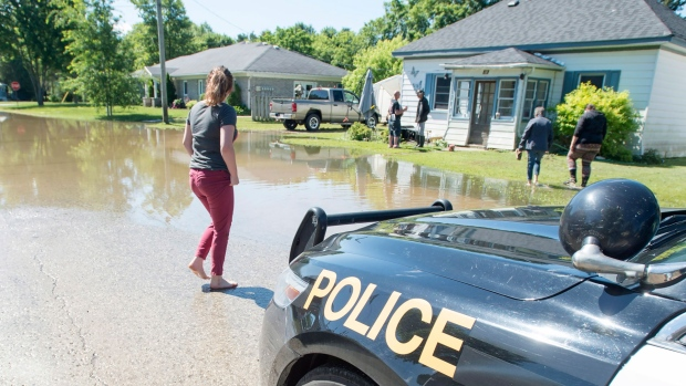 Residents gather on a neighbour's lawn to catch up on the latest news about the flood. in Harriston, Ont., Saturday, June 24, 2017. The extreme water levels flooded dozens of basements and a Public Works Department building. THE CANADIAN PRESS/Adam Gagnon