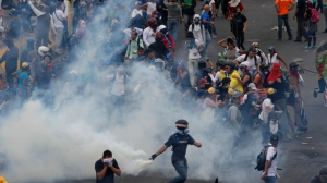Demonstrators clash with authorities, on the fence of La Carlota Air Base in Caracas, Venezuela, Friday, June 24, 2017. (AP Photo/Ariana Cubillos)