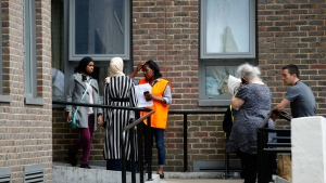 People gather outside Dorney block, part of the Chalcots Estate in the borough of Camden, north London, Saturday June 24, 2017, after the local council evacuated some 650 homes overnight. The apartments were evacuated overnight after fire inspectors concluded that the buildings, in north London's Camden area, were unsafe because of problematic fire doors, gas pipe insulation, and external cladding similar to that blamed for the rapid spread of a fire that engulfed Grenfell Tower on June 14. (AP Photo/Alastair Grant)