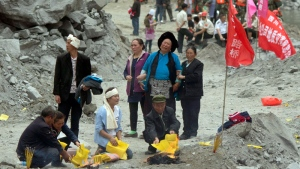 Relatives burn incense and paper offerings to appease the dead at the site of a landslide in Xinmo village in Maoxian County in southwestern China's Sichuan Province, Sunday, June 25, 2017. (AP /Ng Han Guan)