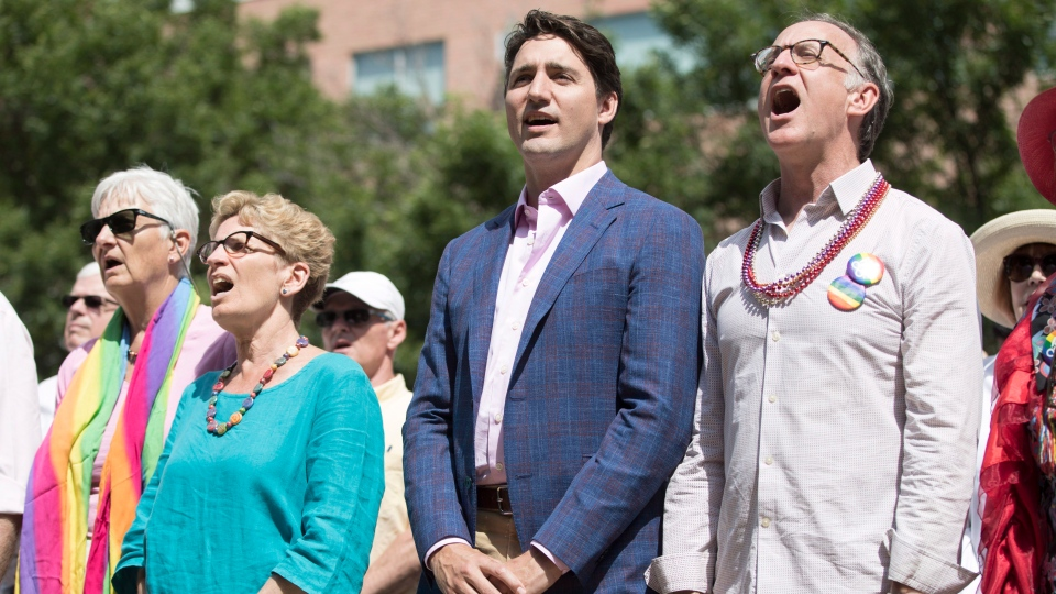 Prime Minister Justin Trudeau (second right), Ontario Premier Kathleen Wynne (second left), Liberal MP Rob Oliphant (right) and Jane Rounthwaite (left), Wynne's partner, sing the national anthem before a Faith + Pride church service in Toronto, Sunday, June 25, 2017. (THE CANADIAN PRESS/Mark Blinch)