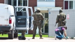 An RCMP investigator collects bullet shells in front of the apartment building where a man retreated inside when RCMP responded to gun shots early Sunday morning on High Street in Moncton, N.B., Sunday, June 25, 2017. (THE CANADIAN PRESS/Marc Grandmaison)