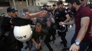 Riot police move to detain a person as they stop protesters for lesbian, gay, bisexual, trans and intersex rights from gathering in large numbers, following a ban issued by the governor, in Istanbul, Sunday, June 25, 2017. (AP Photo/Emrah Gurel)