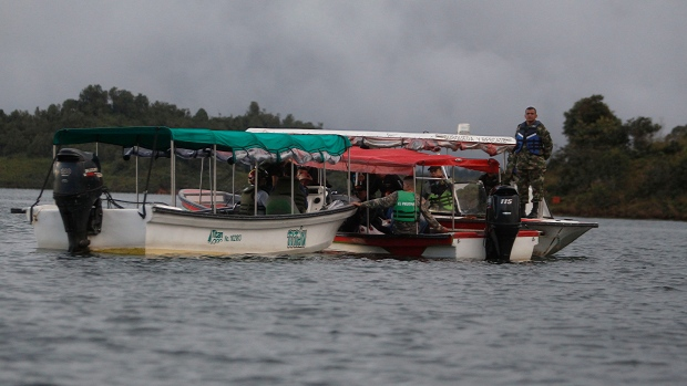 Soldiers and rescue workers flat at the site where a ferry sank in a reservoir in Guatape, Colombia, Sunday, June 25, 2017. Nine people were dead and 28 missing after a tourist ferry packed with around 170 passengers for the holiday weekend capsized Sunday on a reservoir near the Colombian city of Medellin, officials said. (AP Photo/Luis Benavides)