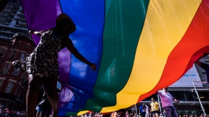 People hold a giant flag during the Pride parade in Toronto, Sunday, June 25, 2017. THE CANADIAN PRESS/Mark Blinch