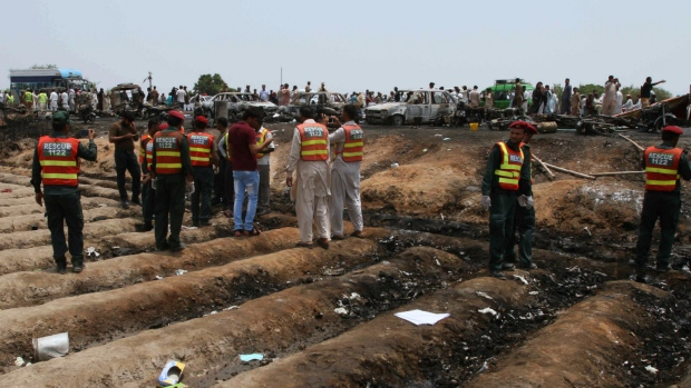 Pakistani rescue workers gather at the site of an oil tanker explosion at a highway near Bahawalpur, Pakistan on Sunday, June 25, 2017. (AP / Iram Asim)