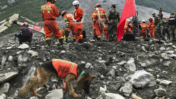 Rescuers with sniffer dogs stand near earthmoving equipment digging at the site of a landslide in Xinmo village in Maoxian County in southwestern China's Sichuan Province on Sunday, June 25, 2017. (AP / Ng Han Guan)
