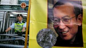 In this Dec. 5, 2010 file photo, a police officer stands guard beside a picture of jailed Chinese dissident Liu Xiaobo outside the Chinese government liaison office in Hong Kong. (AP Photo/Kin Cheung, File)