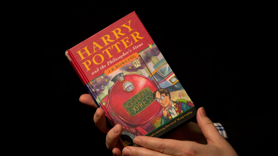 "Sotheby's director of the department of printed books and manuscripts Dr Philip Errington poses for photographers with a first edition copy of the first Harry Potter book ""Harry Potter and the Philosopher's Stone.""  (AP Photo/Matt Dunham)"