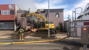 A track hoe knocks down a portion of the front of a building, as crews battled a fire inside, on 101 Ave. and 73 St. Monday, June 26, 2017.