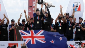 Emirates Team New Zealand helmsman Peter Burling, left, and teammate Glenn Ashby hold the Americas Cup aloft as they celebrate with teammates after defeating Oracle Team USA in the America's Cup sailing competition in Hamilton, Bermuda, Monday, June 26, 2017. (AP Photo/Gregory Bull)