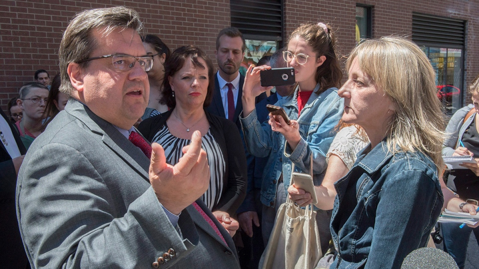A local resident confronts Montreal Mayor Denis Coderre and Lucie Charlebois, centre, Minister for Rehabilitation, Youth Protection, Public Health and Healthy Living, during the opening of a safe injection site Monday, June 26, 2017 in Montreal. (THE CANADIAN PRESS/Paul Chiasson)