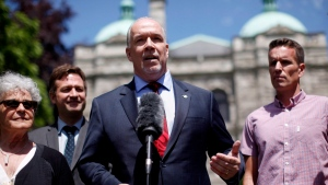 B.C. NDP Leader John Horgan speaks to media as he's joined by (from left to right), Leslie McBain, Rob Fleming and Jason Gammon during a press conference from the Rose Garden at B.C. Legislature in Victoria, B.C., on Monday, June 26, 2017. (Chad Hipolito / THE CANADIAN PRESS)