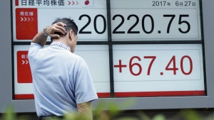 A man looks at an electronic stock board showing Japan's Nikkei 225 index at a securities firm in Tokyo on Tuesday, June 27, 2017. (AP / Eugene Hoshiko)