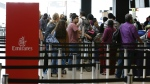 Travellers wait in line near an Emirates ticket counter at the Seattle-Tacoma International Airport in Seattle on Monday, June 26, 2017. (AP / Ted S. Warren)