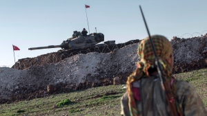 In this February 22, 2015, file photo, a Syrian Kurdish militia member of the YPG patrols near a Turkish army tank as Turks work to build a new Ottoman tomb in the background in Esme village in Aleppo province, Syria. Turkey. (AP Photo/Mursel Coban, Depo Photos)