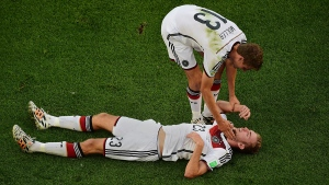 Germany's Christoph Kramer lies on the pitch as teammate Thomas Mueller assists him, during the World Cup final soccer match between Germany and Argentina at the Maracana Stadium in Rio de Janeiro, Brazil, Sunday, July 13, 2014. (AP Photo/Francois Xavier Marit, Pool)