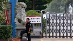 FILE -- In this June 18, 2017, photo, a security guard smokes near a main entrance gate of the Ganzhou Huajian International Shoe City Co.'s factory, which has made shoes for the Ivanka Trump brand, in Ganzhou in southern China's Jiangxi Province. (AP Photo/Andy Wong)