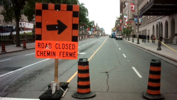 A sign and cones block Wellington St. at Bank St., site of the first road closure for Canada Day preparations. The closure caused massive backups for traffic, including OC Transpo buses. (Jim O'Grady/CTV Ottawa, June 27, 2017)