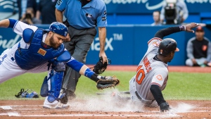 Baltimore Orioles' Adam Jones beats Toronto Blue Jays catcher Russell Martin to the plate to score during first inning MLB baseball action in Toronto, Tuesday June 27, 2017. (THE CANADIAN PRESS/Mark Blinch)
