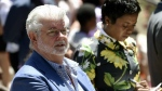 Filmmaker George Lucas, left, and his wife Mellody Hobson listen to remarks at a news conference outside Los Angeles City Hall on Tuesday, June 27, 2017. (AP / Chris Pizzello)