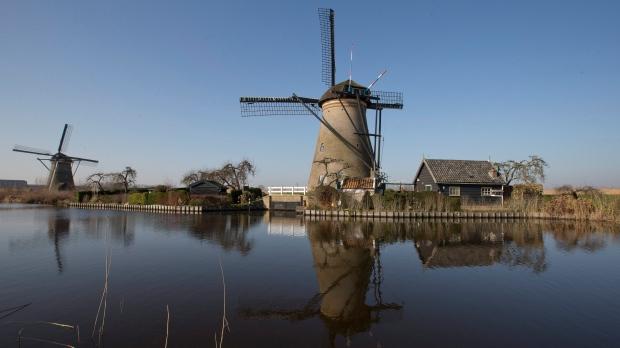 In this Feb. 14, 2017, file photo, windmills line Hooge Boezem van de Overwaard canal at the Unesco World Heritage site in Kinderdijk, Netherlands. (AP Photo/Peter Dejong, File)