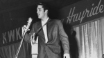 In this Dec. 15, 1956 file photo, Rock-n-Roll legend Elvis Presley entertains a packed house as a headlining act during a special performance of the KWKH Louisiana Hayride at Hirsch Coliseum in Shreveport, La. (Langston McEachern/The Shreveport Times via AP)
