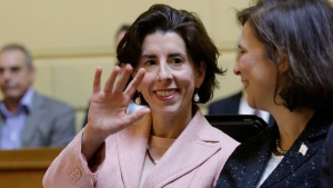 Rhode Island Gov. Gina Raimondo, centre, waves while seated next to R.I. Secretary of State Nellie Gorbea, right, while attending swearing-in ceremonies Tuesday, Jan. 3, 2017. (AP Photo/Steven Senne)
