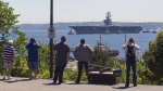 Onlookers watch as the aircraft carrier, USS Dwight D. Eisenhower, prepares to anchor following its arrival in Halifax, Wednesday, June 28, 2017. Launched on Oct. 11, 1975, the 86,000-tonne carrier is the second-oldest Nimitz-class vessel in the U.S. navy's fleet and has a crew of up to 6,200 sailors and airmen.THE CANADIAN PRESS/Stringer