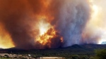 In this Tuesday, June 27, 2017 frame from video, flames and smoke rise from a fire near Mayer, Ariz. The Arizona fire forced the evacuation of Mayer along with several other mountain communities in the area. (Jennifer Johnson via AP)