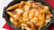 A dish of poutine (left) and poutine topped with bacon from a Burger King restaurant are shown in Toronto, Tuesday, May 12, 2015. THE CANADIAN PRESS/Frank Gunn
