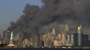 FILE -- In this Sept. 11, 2001 file photo, thick smoke billows into the sky from the area behind the Statue of Liberty, lower left, where the World Trade Center towers stood. (AP Photo/Daniel Hulshizer)