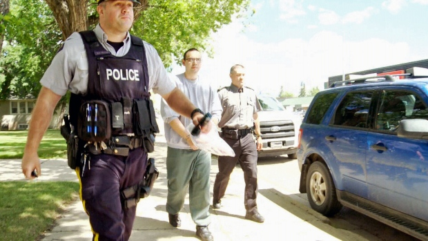 Steven Lewis, centre, is escorted out of Melfort Provincial Court on Wednesday, June 28, 2017, after pleading guilty to second-degree murder in his ex-wife's death. He was sentenced to life in prison with no chance of parole for 22 years after entering the plea.